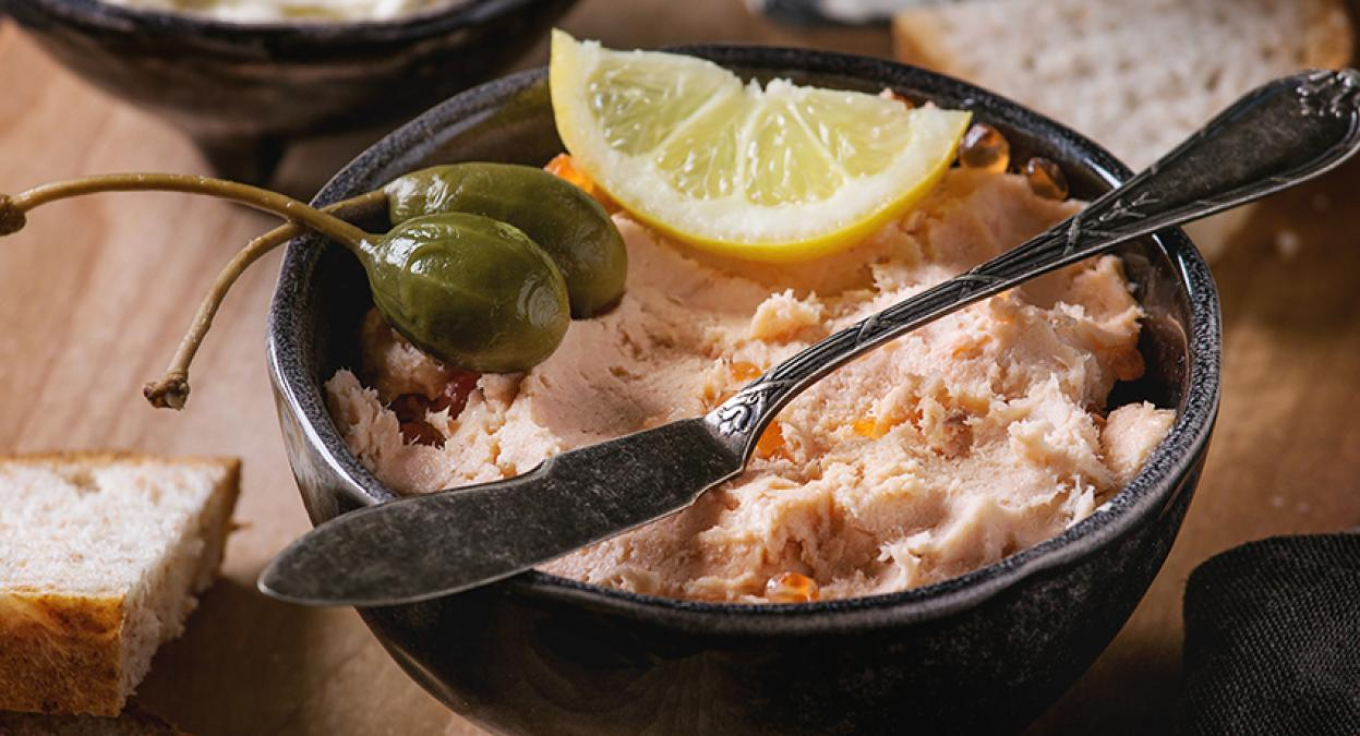 Salmon pate in a bowl with a lemon