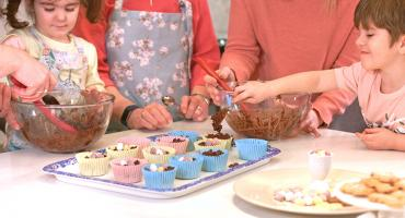 Children decorating Easter egg nest cakes