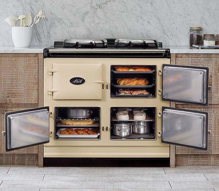 AGA cooker in cream with AGA cookware inside